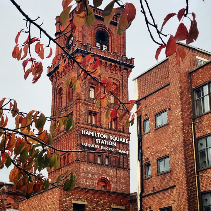 Red brick tower above Hamilton Square station advertising 'frequent electric trains'.