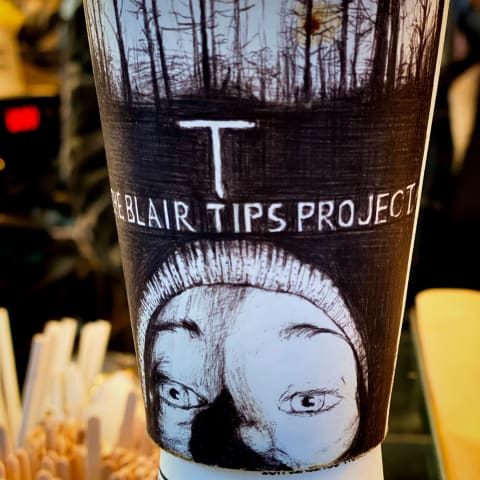 Paper coffee cup thats says 'The Blair Tips Project'.
