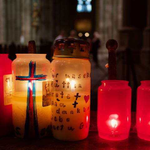 Candles inside coloured jars within a dark Cologne Cathedral.
