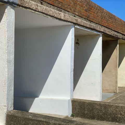 Harsh shadows on concrete beach shelters.