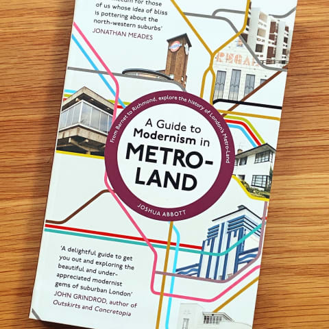 'A Guide to Modernism in Metroland' book on a wooden desktop.