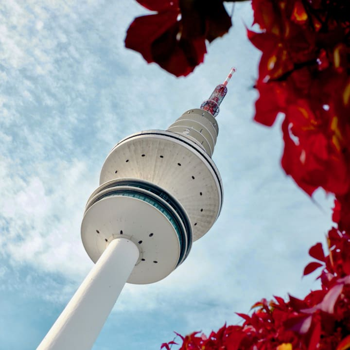 Hamburg's TV Tower taken from a viewpoint that surrounds it with red leaves.