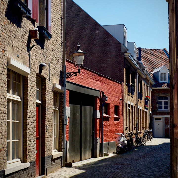 View down Ridderstraat, with colourful red walls and doors, with bikes parked to one side.