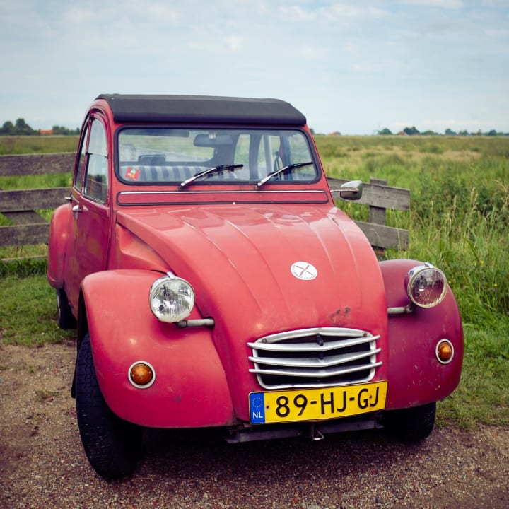 A red Citreon 2CV parked by a green field.