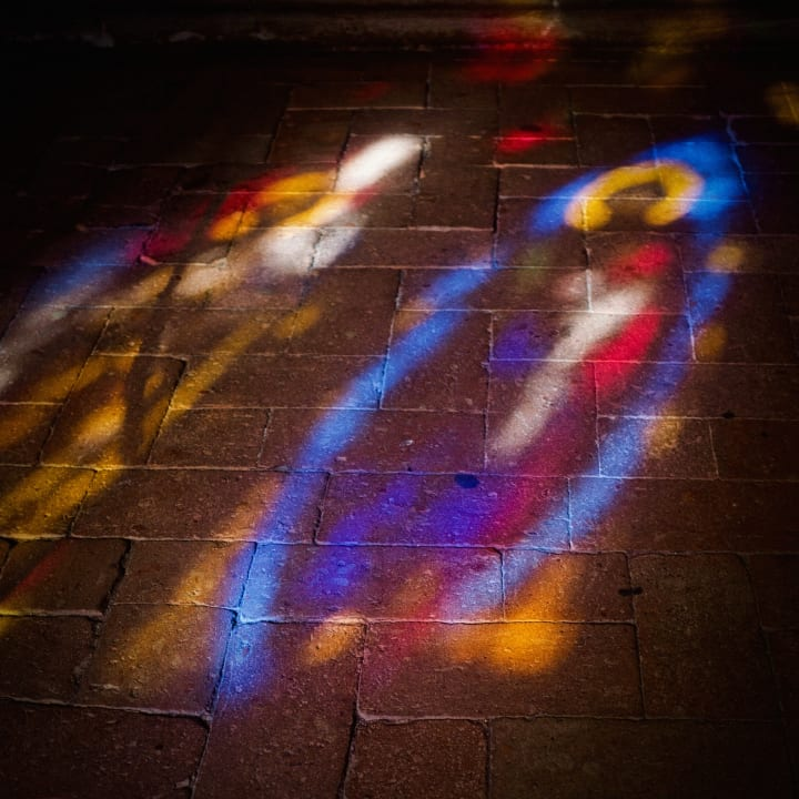 Light from a stained glass window reflected on a stone floor.