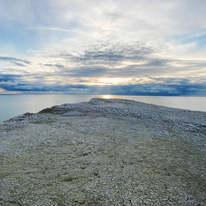 Chalk cliff edge against a dramatic sky.