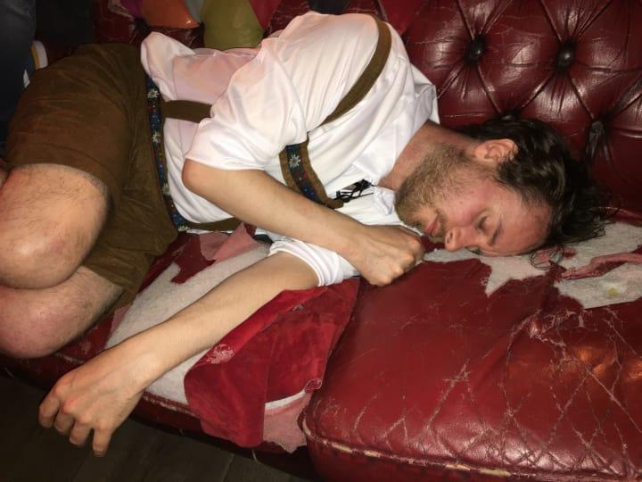 Andy asleep on a pub sofa wearing lederhosen