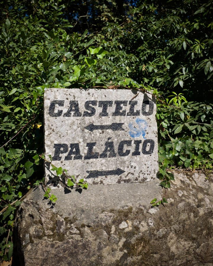 Painted sign pointing to 'Castelo' (left) and 'Palácio' (right).