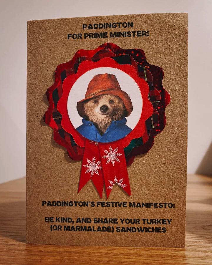 A Christmas card featuring a photo of Paddington Bear on a political rosette.