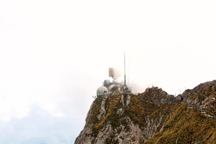 Radar station poking through clouds atop a mountain range.