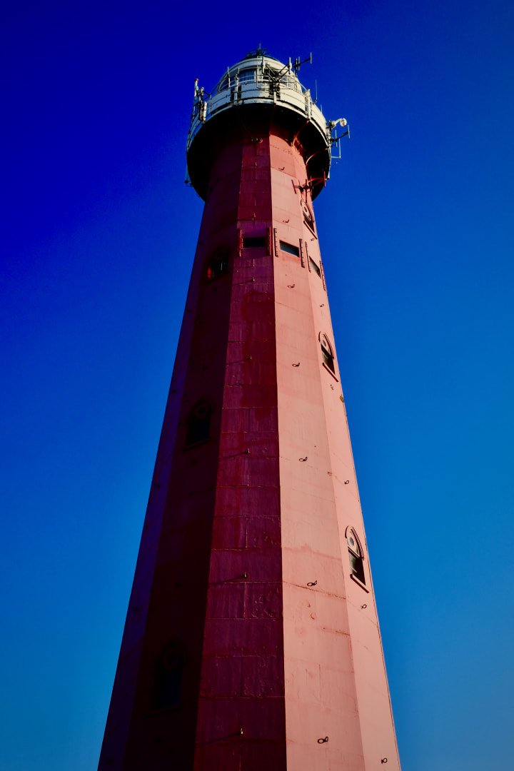 Looking up at a tall red lighthouse.