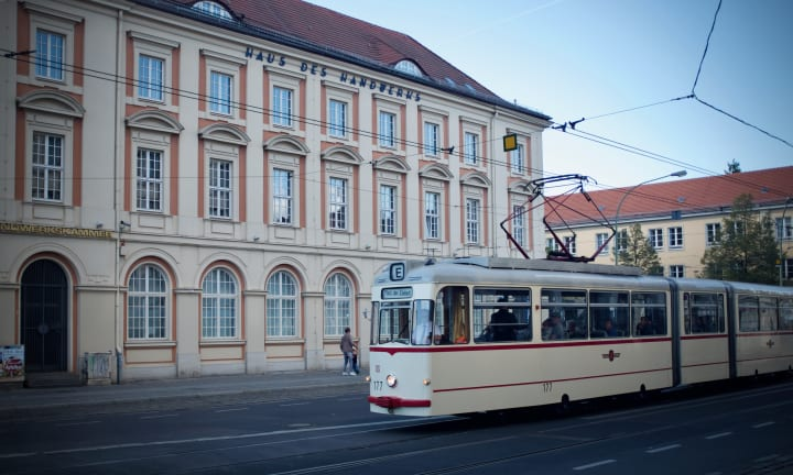 White tram passes in front of a cream building.