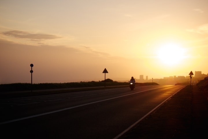 Motorbike on a road leaving Brighton at sunset.