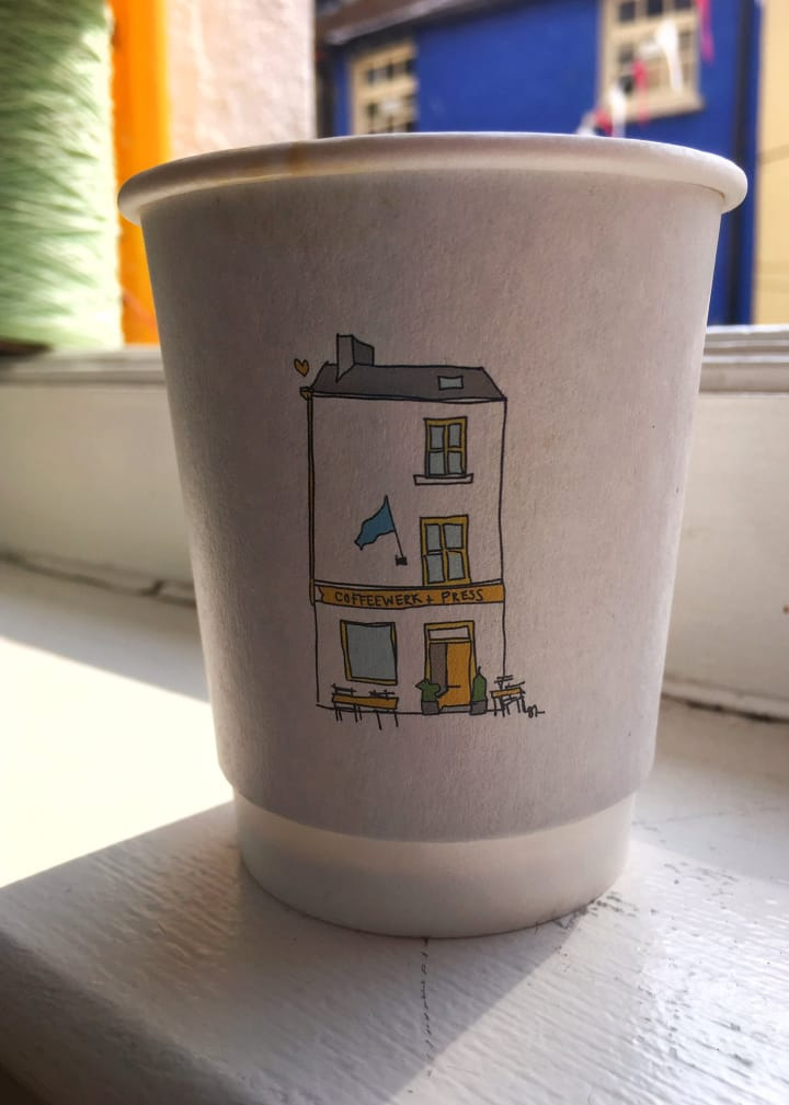Paper cup with an illustration of the Coffeework + Press building on its side.