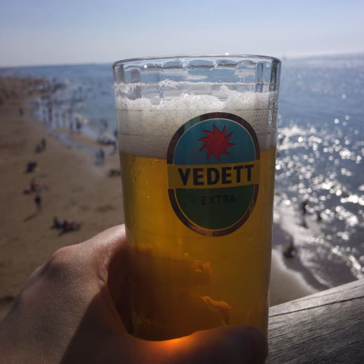 Pint of Vedett beer with Scheveningen beach in the background.