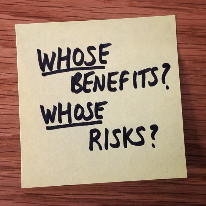 """Post-it note that reads """"Whose benefits? Whose risks?""""."""