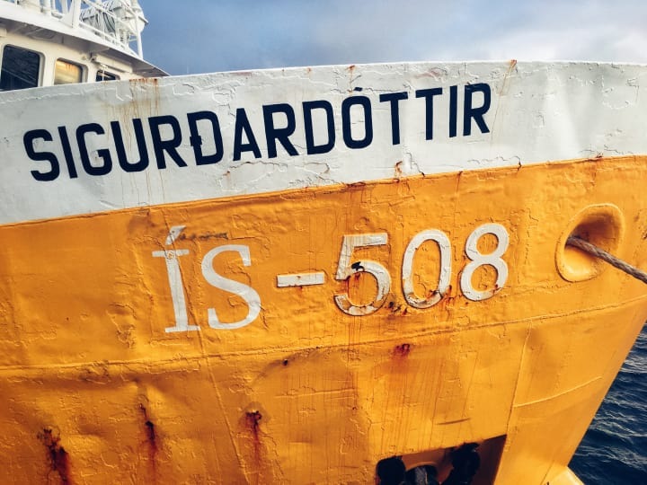 Yellow hull of a fishing boat with identification number ÍS-508.