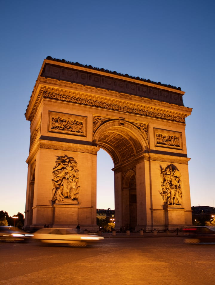 An illuminated Arc de Triomphe as dusk falls.