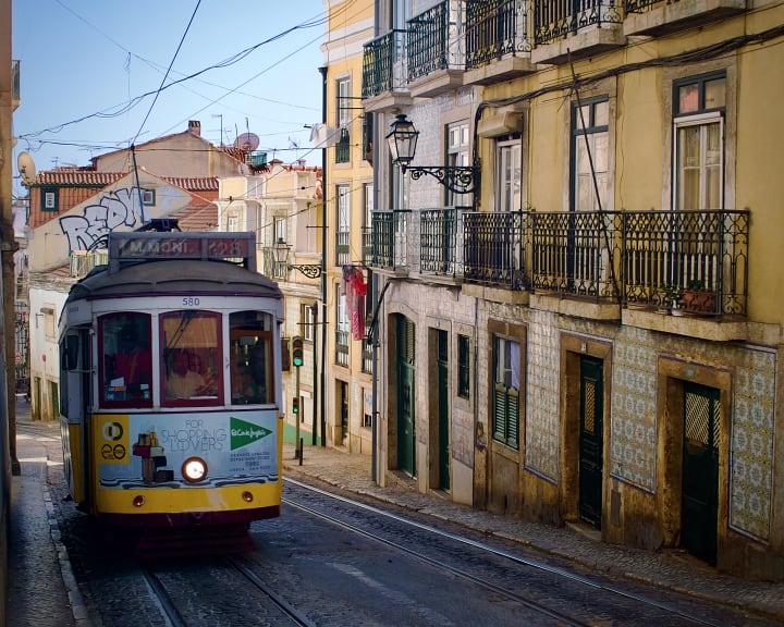 Tram travelling down a narrow street.
