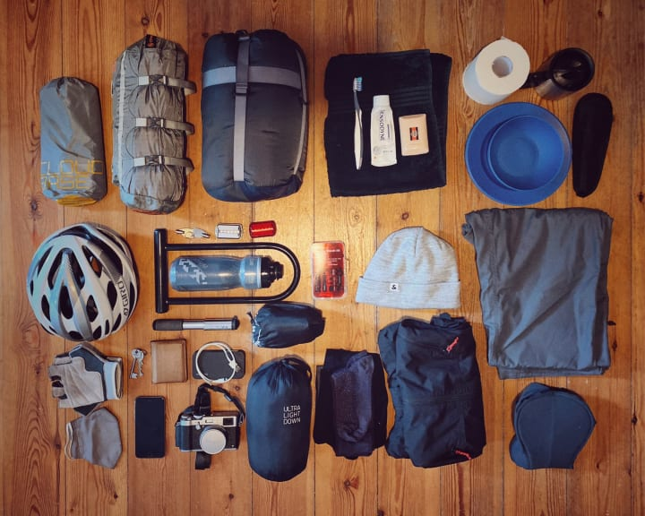 Camping and cycling gear laid out on a wooden floor.