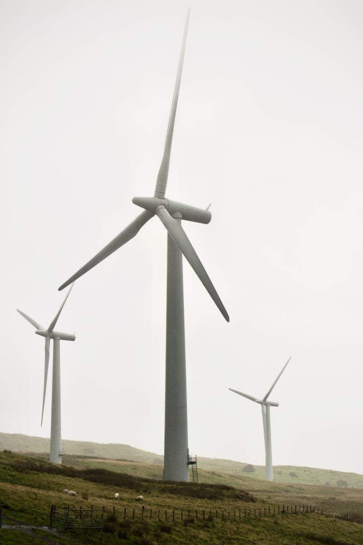 Three large wind turbines tower above a misty moorland.