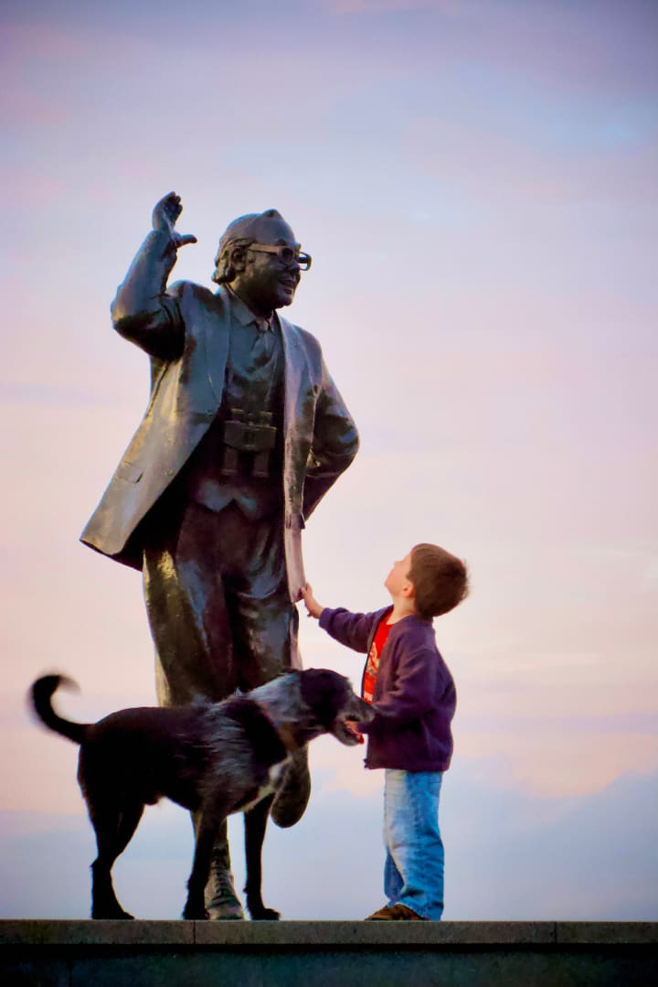 A young child tugs on the coat of Eric Morecambe, a dog stood next to him.
