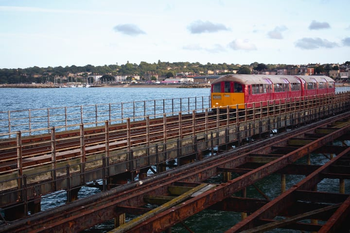 A red coloured former tube train travels over a stretch of pier.