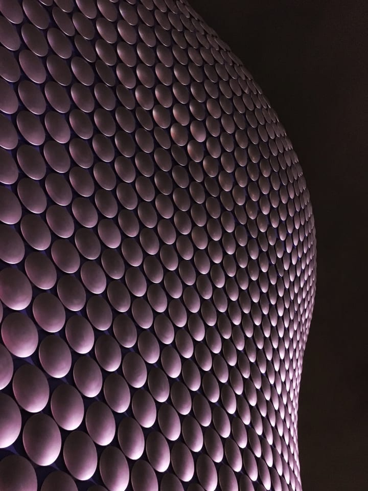 Cirucular discs covering the curvy Selfridges building indirectly illuminated at night.