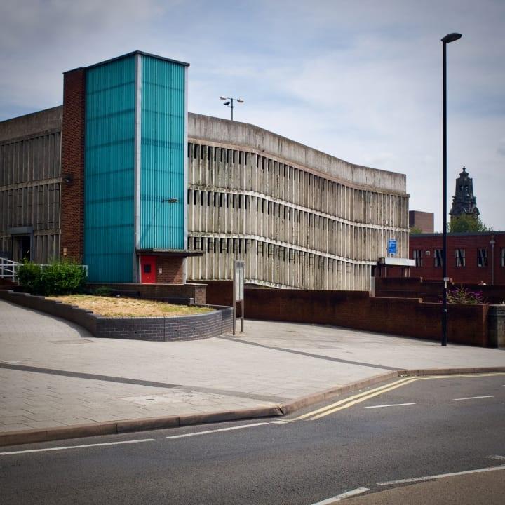 A brutalist looking concrete multi-storey car park.