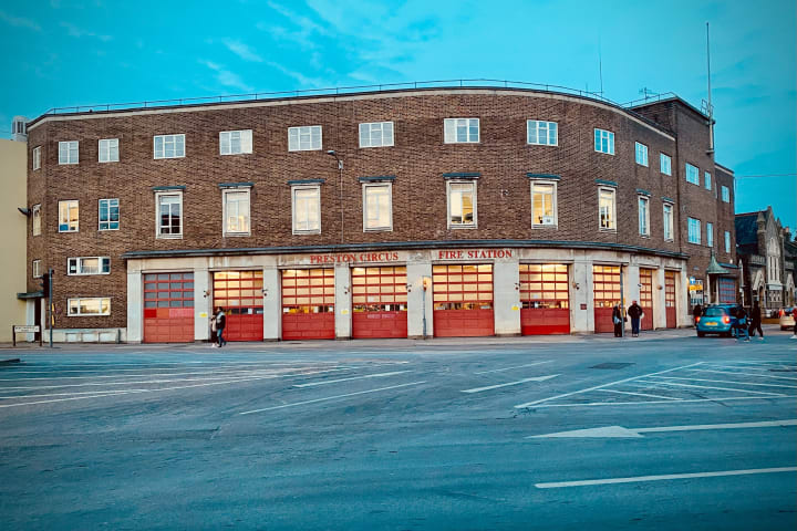 Three storey fire station on the corner of a traffic junction.