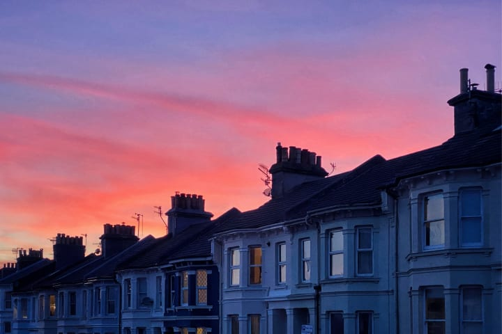 Vivid sunset over a row of terraced houses.