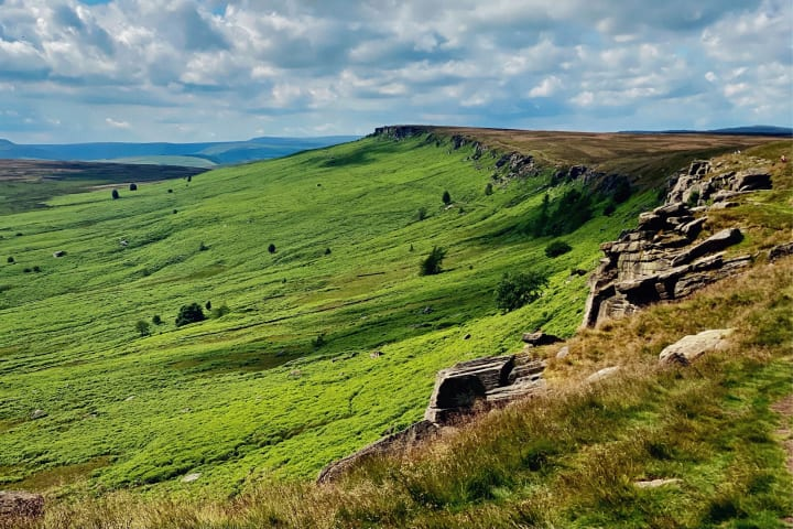 Ridge line contrasting with green moorland bordering it.