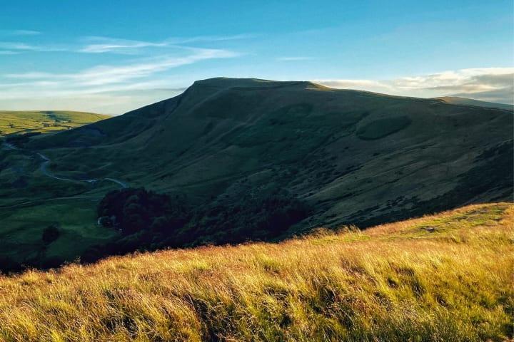 Sunlight casting Mam Tor as dark against bright foreground moorland.
