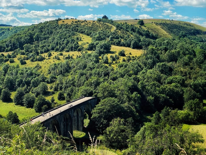Disused railway viaduct crossing a valley.