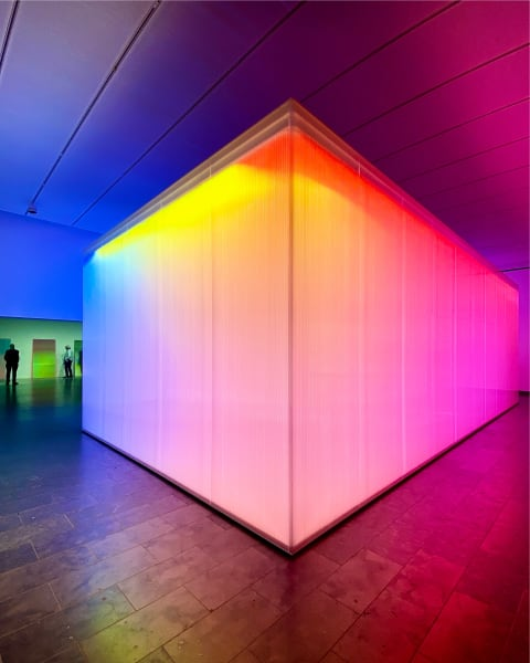 Colourful, glowing box in the middle of a gallery.