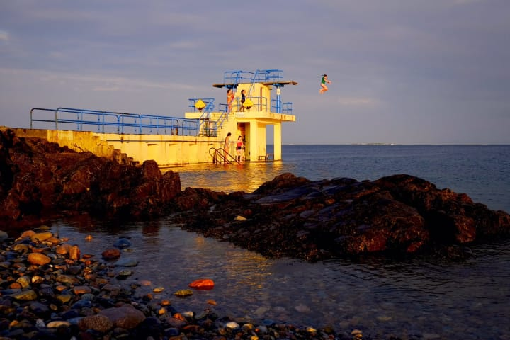 Person jumping off the Blackrock Diving Tower in Salthill