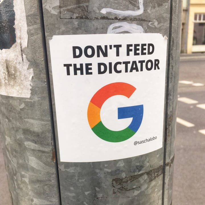 "Sticker featuring the Google 'G' monogram which reads ""Don't feed the dictator""."
