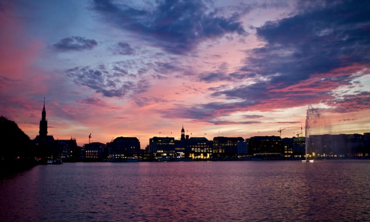 Vivid sunset over Binnenalster with cityscape in the distance.