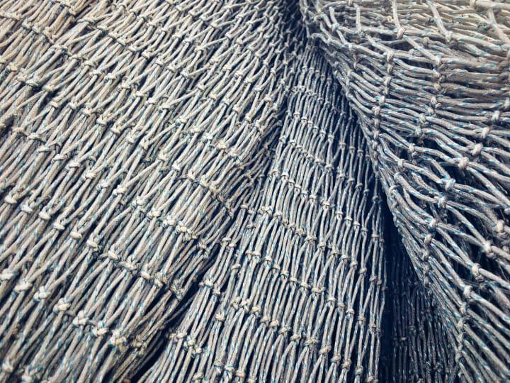 Closeup detail of stacked grey fish nets