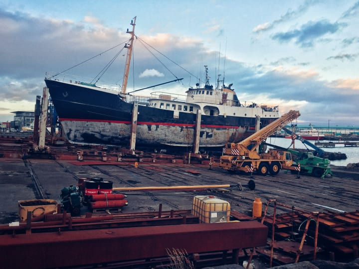 A boat in dry dock being repaired.