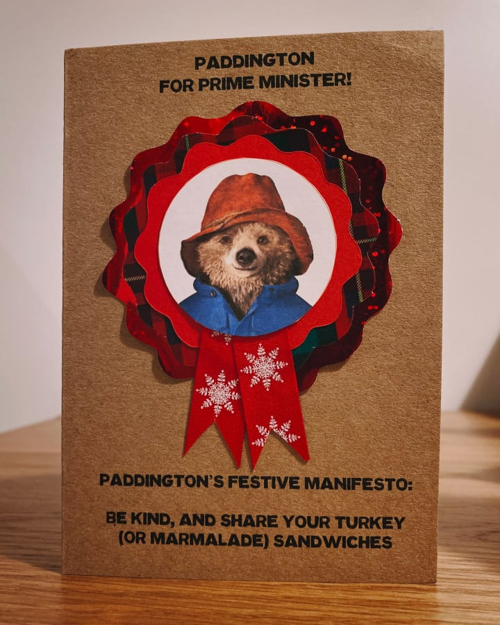 A Christmas card featuring a photo of Paddington Bear on a political rosette.