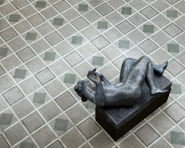Bronze sculpture of a woman lying on her side, viewed from above.