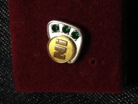 """10k gold pin """"Ni"""", Precious Metal or Stones, 10k white gold and yellow gold, 3 small emeralds, 10k white gold and 10k yellow gold, """"Ni"""" on the front"""