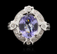 """14KT White Gold 2.69 ctw Tanzanite and Diamond Ring, Jewelry, 2.69 CTW, One electronically tested 14KT white gold ladies cast tanzanite and diamond ring with a bright polish finish. The featured tanzanite is set within a stylized diamond bezels supported by grooved shoulders, completed by a three millimeter wide band. Identified with markings of """"14K"""". Condition is new, good workmanship. Containing: One prong set oval mixed cut natural tanzanite, measuring 10.80 x 8.40 x 4.10mm, approximate weight of 2.69ct., clarity is eye clean, type I, medium, very slightly grayish, bluish violet color, (GIA bV 5/3), cut is good. Transmitting light with no distortion, transparent. Graded in the setting. Tanzanite is a very rare gemstone that is only found in the country of Tanzania. Originally discovered in 1967. Tiffany & Company, named the stone Tanzanite. It is found in the Usumburu Mountains that border the Umba Valley of northern Tanzania. Tanzanite occurs in gray, brown, violet, blue, reddish-purple, & green. The gem is interesting because of its exceptional pleochroism. Rotated in different directions a tanzanite will exhibit multiple changes of color. Tanzanite has a low tolerance to ultrasonic cleaning, and should not be cleaned using this method. Sixteen prong & flush set round brilliant cut diamonds, measuring 1.80 - 1.60 x 1.02mm (depth est.) approximate. Total Weight of 16 Stones = 0.33ct. Graded in the setting. Clarity: SI-2 to I-2 . Color: H - J. Total Weight of Colored Stones 2.69ct.. Total Weight of Diamonds 0.33ct. AIG Appraised at $7,515.00."""