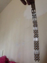its a mens bracalet, Precious Metal or Stones, white and gold , well i dont know if it diomond but they told me it is