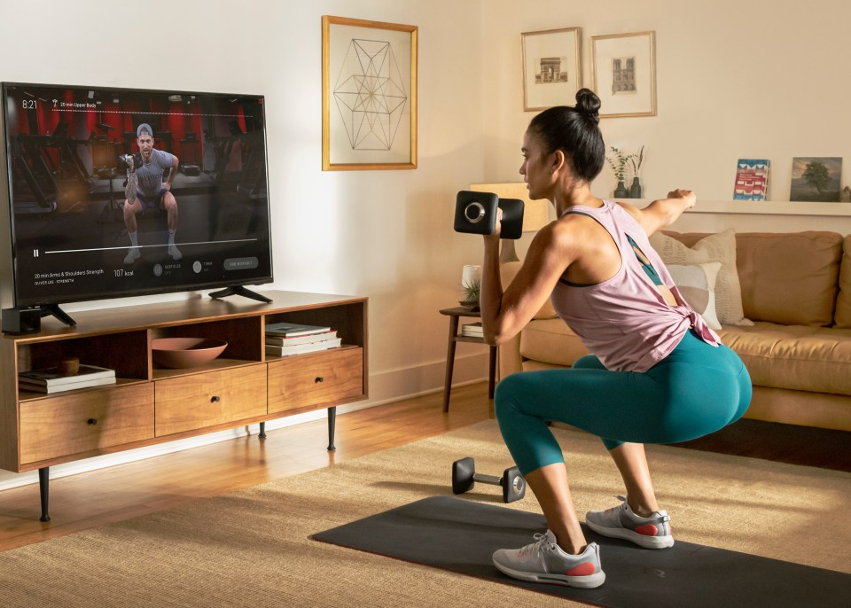 Woman using hand weights for a home workout using the Peloton home app.