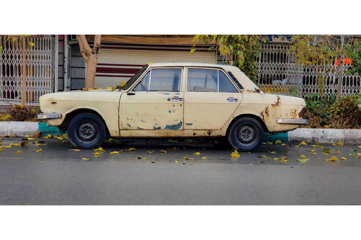 Old used car parked on a street.