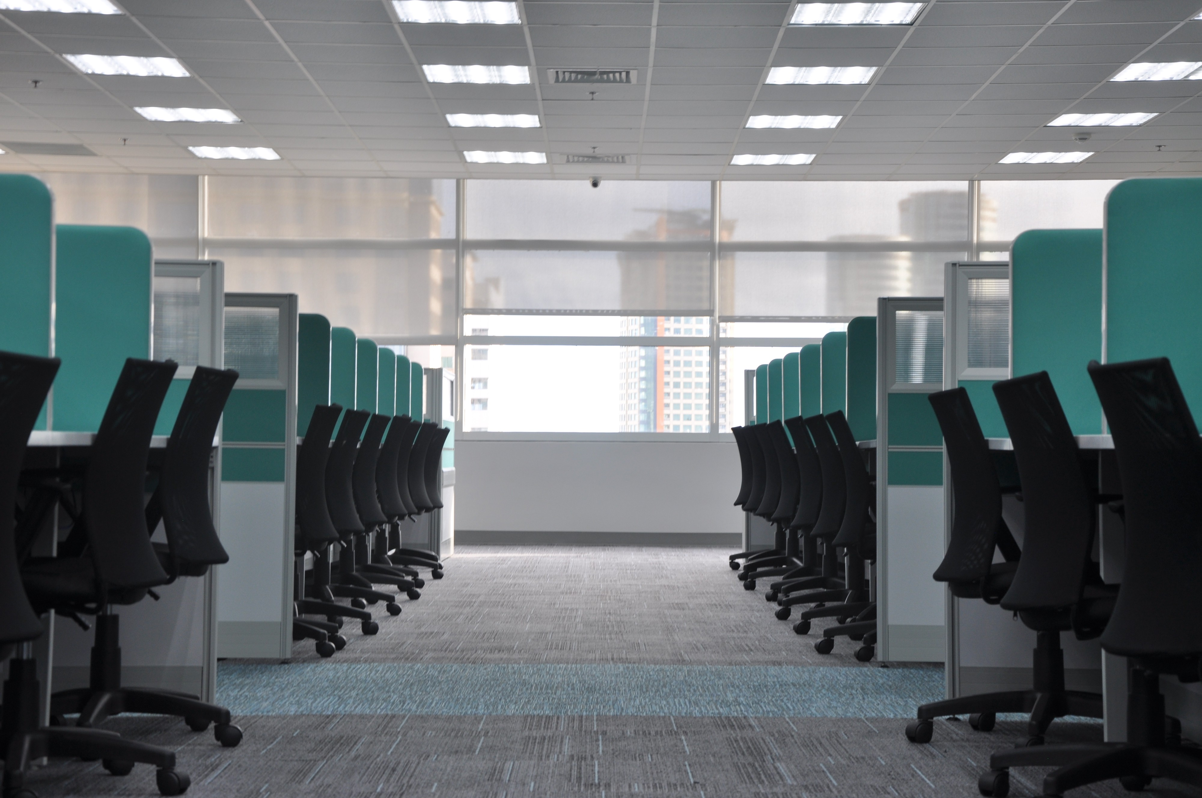 A row of chairs and cubicles inside an office building.