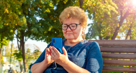 Women looking at her digital balance while sitting in the park