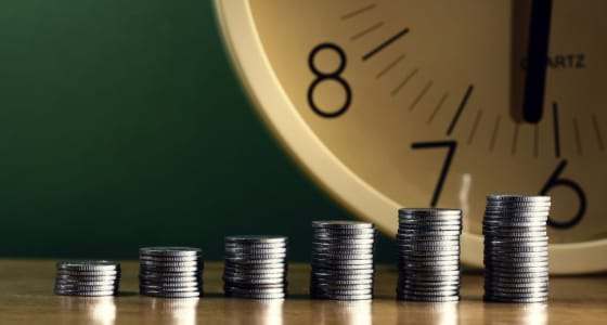 Several stacks of coins increasing in height from left to right with a clock in the background